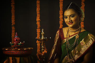 Portrait of Indian woman celebrating the festival called Diwali by Lighting the traditional lamps. - Royalty free stock photo, image