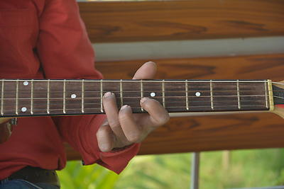Close of hand and fingers playing guitar strings and frets, selective focusing - Royalty free stock photo, image