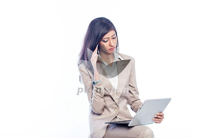 Woman trying to solve problem in office - Royalty free stock photo, image