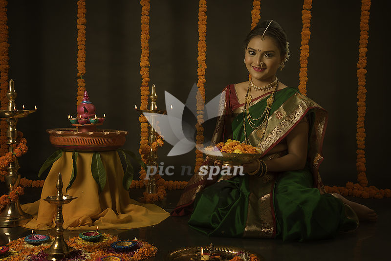 Portrait of Indian woman celebrating Diwali festival by lighting the lamps - Royalty free stock photo, image